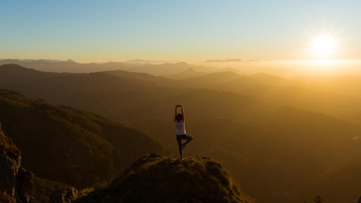 Woman doing yoga stance on top of a mountain